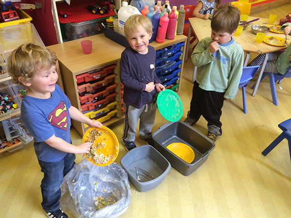 Helping to clear the lunch plates at Acorns Nursery School, Cirencester.