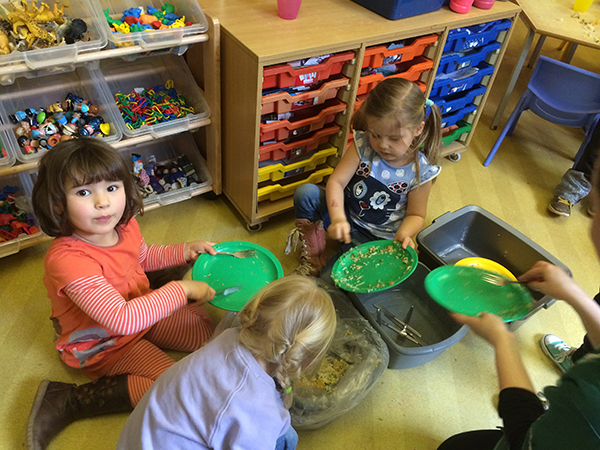 Helping to clear the plates ready for washing up at Acorns Nursery School, Cirencester.