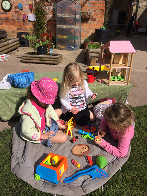 Playing on the grass in the garden at Acorns Nursery School, Cirencester.