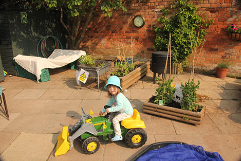 Gardening with the (toy) tractor at Acorns Nursery School, Cirencester.