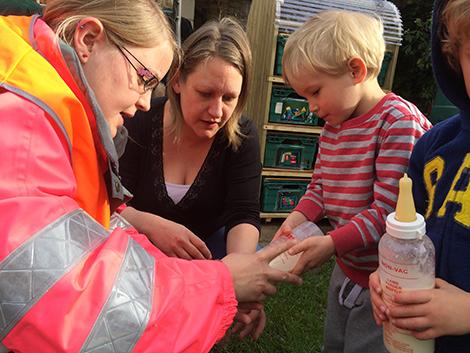 Feeding the lambs in the garden at Acorns Nursery School Cirencester