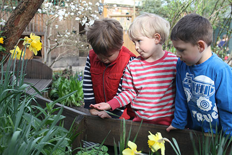 Examining the bug in the garden at Acorns Nursery School, Cirencester.