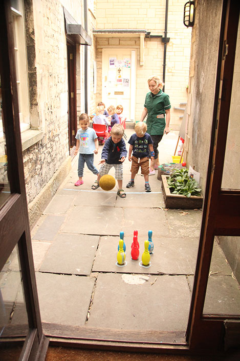 Playing skittles in the pre-school courtyard classroom at Acorns Nursery School, Cirencester.